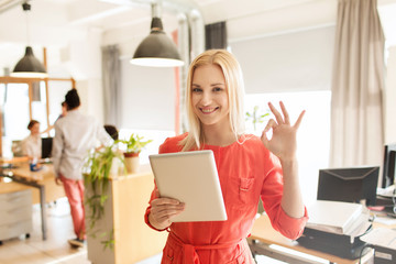 woman with tablet pc showing ok sign at office