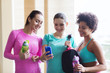 happy women with bottles and smartphone in gym