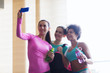 happy women with smartphone taking selfie in gym