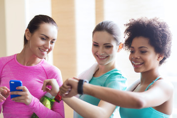 happy women showing time on wrist watch in gym