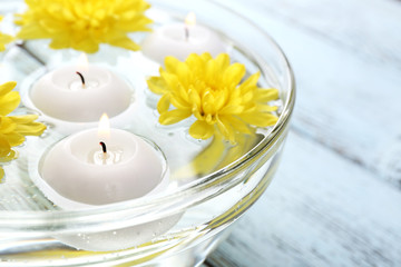 Bowl of spa water with flowers and candles