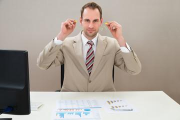 Businessman Inserting Earplug In Ears