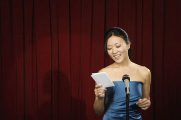 Asian woman reading card on stage
