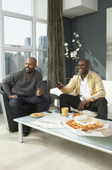 African men watching television and eating pizza in living room