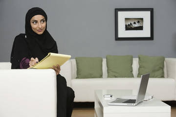 Middle Eastern businesswoman writing on notepad