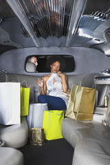 African woman with shopping bags in limousine