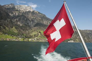 """Schiff mit Schweizfahne, im Hintergrund das Dorf """"Bauen"""" UR"""