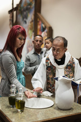 Priest and woman performing baptismal rites in church
