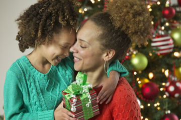Black mother and daughter holding Christmas gift