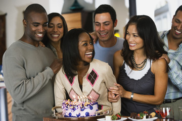 African woman celebrating birthday with multi-ethnic friends