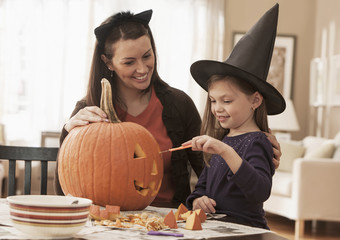 Caucasian mother and daughter carving pumpkin