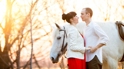 Romantic retro dating. Grazing horse on the background.