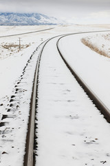 Snow-Covered Railroad Tracks in Rural Landscape