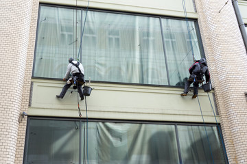 Two men cleaning windows service on high rise building