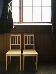 Two Empty Chairs Beneath a Window