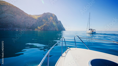 Yachts sailing along the shore in the sea. - 82125072