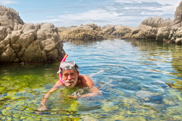 Old man doing snorkelling