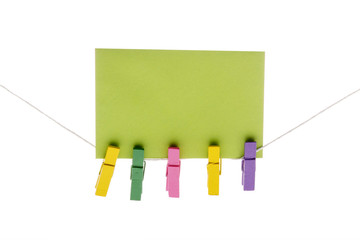 Detail of colorful pegs on rope holding green message card