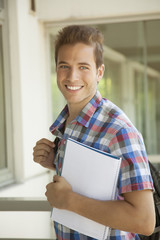Happy young student man with folder