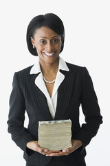 African businesswoman holding stack of money