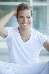 Happy young blonde man relaxing outdoors