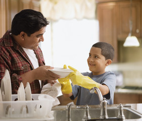 Hispanic father and son washing dishes