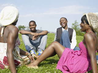 Laughing African friends sitting in park