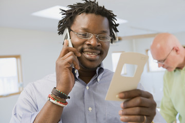 African interior designer looking at paint swatch and talking on cell phone