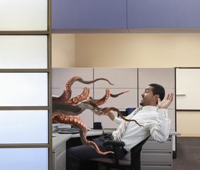 Octopus attacking businessman at desk