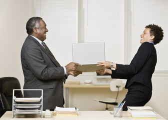 African businesspeople having tug-of-war with laptop