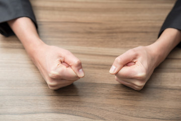 two businesswoman's fists on a wood table