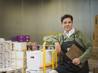 Hispanic worker carting boxes in walk-in freezer