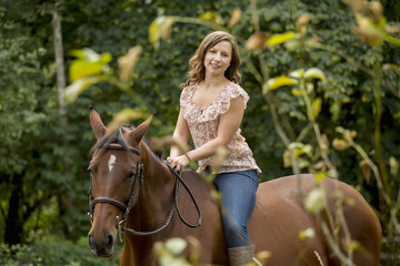 Caucasian woman riding horse outdoors