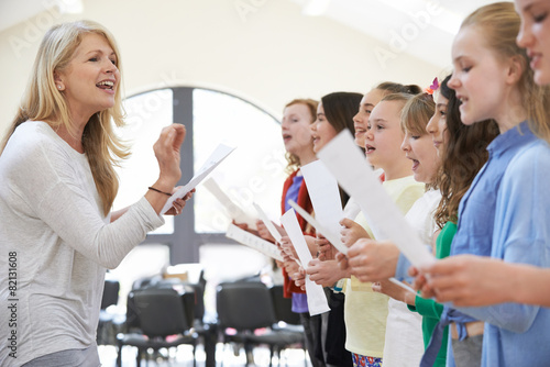 Children In Singing Group Being Encouraged By Teacher - 82131608