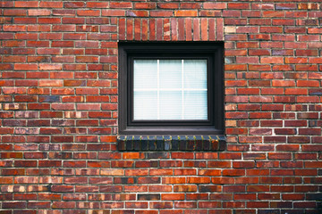 A brick wall with a small square window