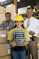 Hispanic woman holding Employee of the Month plaque