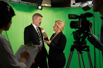Female Presenter Interviewing  In Television Studio With Crew In