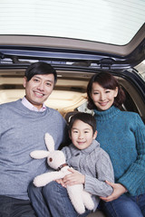 Chinese family sitting in back of car