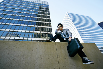 Asian businessman sitting on ledge in city