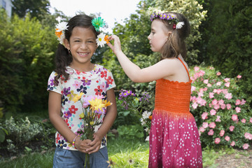 Girls playing with flowers in grass