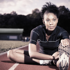 African American runner stretching on track
