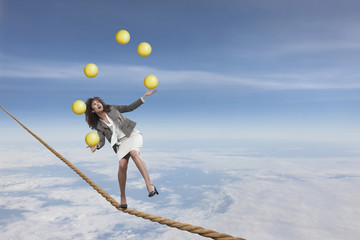 Mixed race businesswoman juggling on tightrope