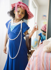 Mixed race girl playing dress-up in mother's clothes