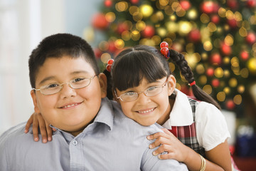 Hispanic brother and sister smiling near Christmas tree
