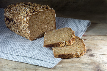 bread loaf with whole grain and seed on rustic wood, dark backgr