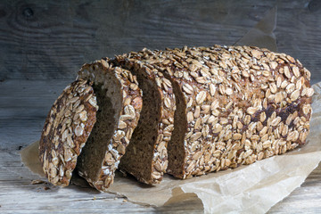 dark bread loaf with whole grain and seeds on an old wooden boar