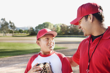 Hispanic baseball player and coach talking