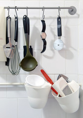 Wrist watch hanging amongst various kitchen tools