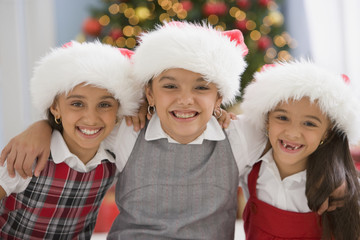 Hispanic sisters wearing Santa Claus hats