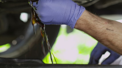 Hands of a mechanic draining car oil